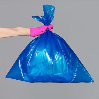 Женская рука в резиновой перчатке держит синий пластиковый пакет, полный мусора.
