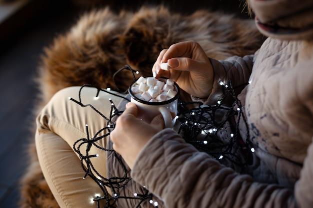 ホットチョコレートとマシュマロの白いエナメルマグカップを保持している彼女の膝の上のクリスマスの花輪を持つ女性。