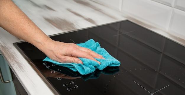 Женская рука с синей салфеткой из микроволокна натирает стеклокерамическую плиту.
