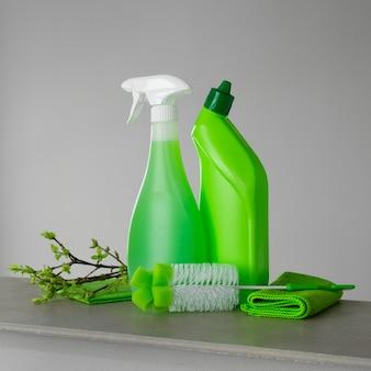 Зеленый набор для весенней уборки и несколько веточек с молодыми весенними листьями.