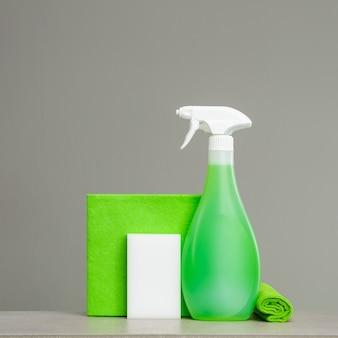 緑色のスプレーボトルをプラスチックディスペンサー、スポンジ、布でほこりを取り除きます。