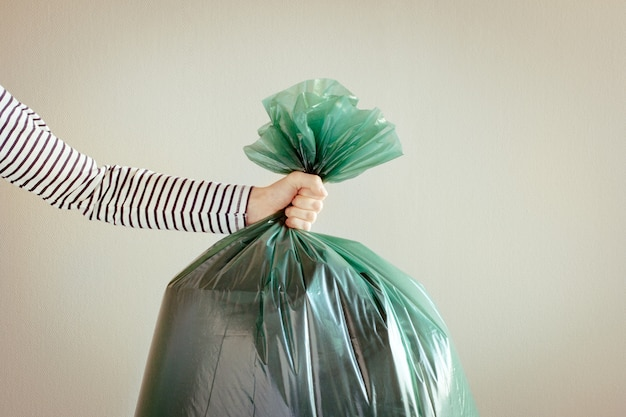 緑のゴミ袋を持つ男の手。中立的な背景。