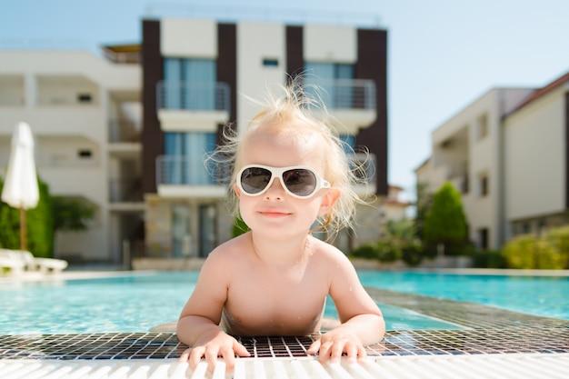 バカンスプールでサングラスを持つ少女のクローズアップの肖像画。
