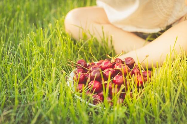 座っている子供の足元の草の上に甘いチェリーでいっぱいのプレート