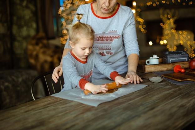 おばあちゃんは孫娘が伝統的なクリスマスジンジャークッキーの生地を出すのを手伝います