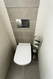 ペーパーホルダーとトイレブラシ付きのモダンなバスルームに白い便器。