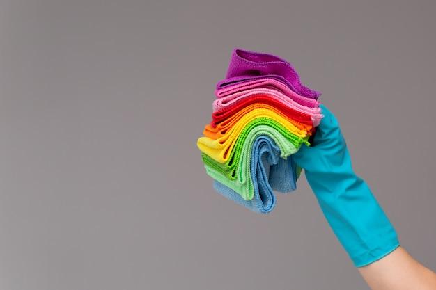 ゴム手袋をはめた手が色付きのマイクロファイバークロスのセットを保持している