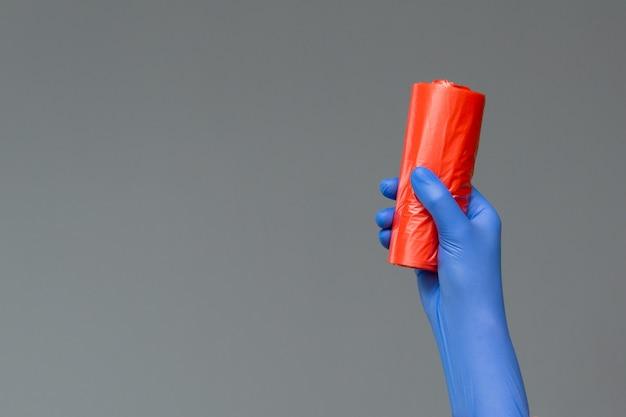 ゴム手袋の手は色のゴミ袋を保持します