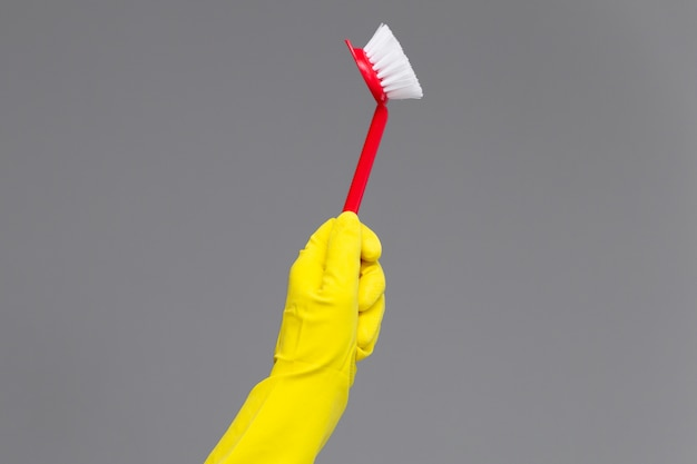 Рука в резиновой перчатке держит щетку для мытья посуды