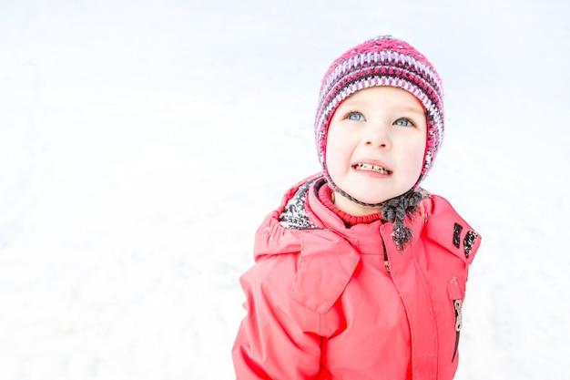 ニット帽子とピンクの冬のジャケットを着た青い目の少女が見上げます。雪の背景。閉じる。