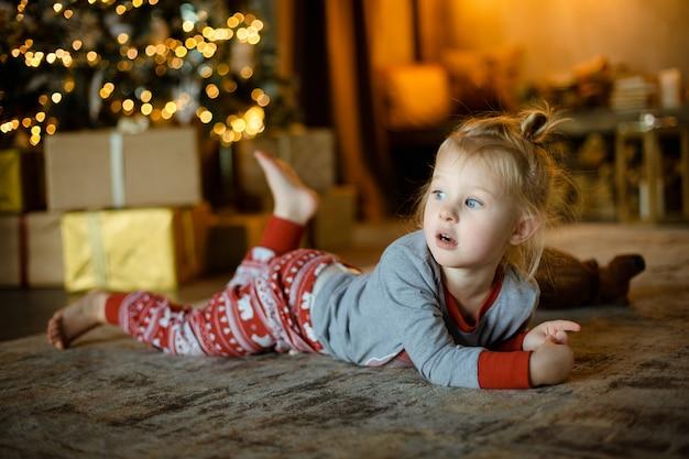 装飾クリスマスツリーと燃える花輪の背景にカーペットの上の魅力的な小さなブロンド。