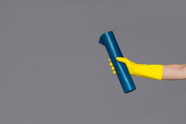 Рука в резиновой перчатке держит синий мешок для мусора на нейтральном фоне. весенняя уборка.