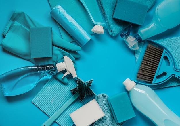 青色の背景に家の春の大掃除のためのツールとクリーニングツールの青いセット。テキストのための場所。