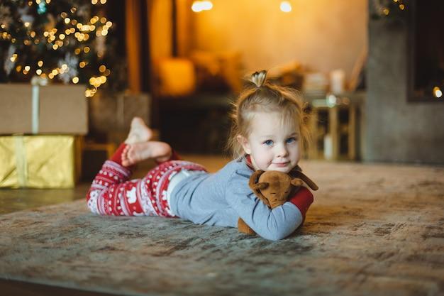 Красивый малыш лежит на полу перед деревом и обнимает свою любимую плюшевую игрушку