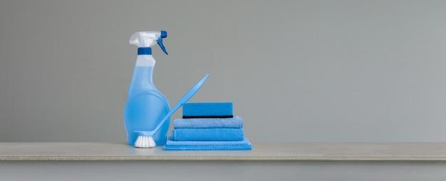 プラスチックディスペンサー、スポンジ、皿のスクラブブラシ、灰色のほこりの布で青いスプレーボトルをクリーニング