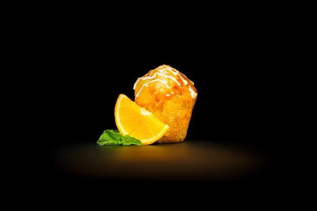 オレンジとミントの葉のスライスとオレンジのマフィン、アイシングでびっしょり