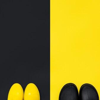 Черные и желтые резиновые сапоги на желтом и черном фоне. вид сверху. яркая и контрастная концепция осени. копировать пространство