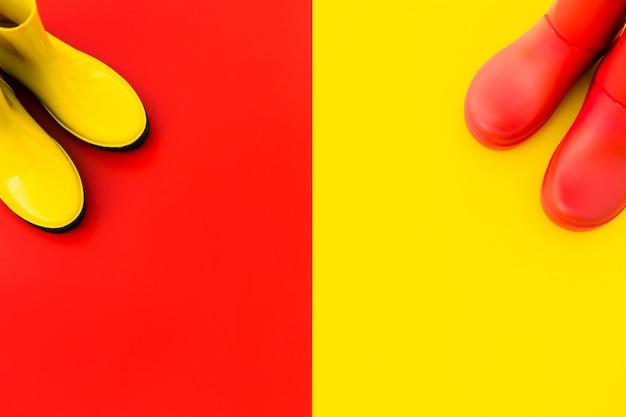 Две пары ярких дождевых сапог стоят на разноцветных фонах напротив друг друга.