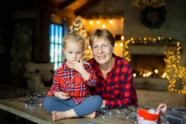 テーブルの上に座ってクリスマスプレゼントのお菓子を食べる小さな孫娘と若い祖母。クリスマス家族の朝のコンセプト。