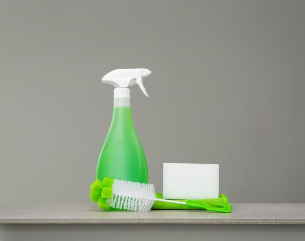Зеленый набор чистящих средств и инструментов для весенней уборки.