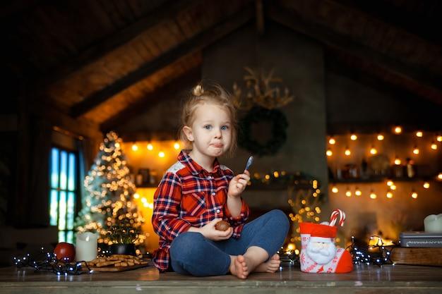木製のテーブルの上に座って、彼女のクリスマスプレゼントからチョコレートの卵を食べる白い金髪少女。