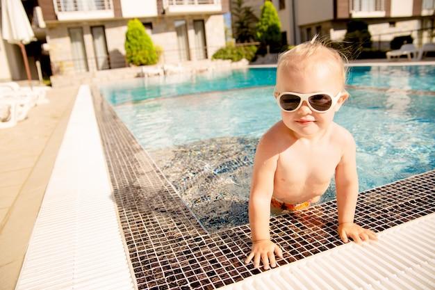 Портрет милая блондинка девочка, вылезая из бассейна.