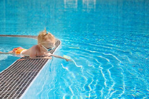 小さなかわいい女の赤ちゃん、プールサイドに横になっていると、水を通して見る。