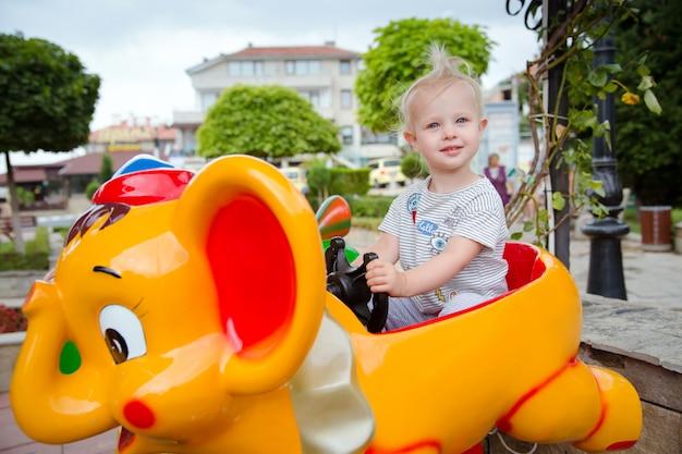 公園の娯楽に乗ってかわいい赤ちゃん女の子
