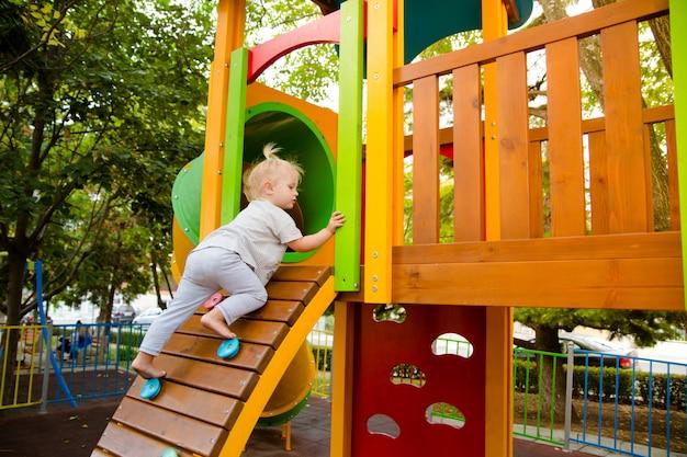 小さな女の子が子供の遊び場のスライドにあるクライミングウォールを登ります。