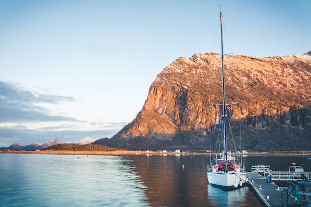 ノルウェーのフィヨルドの浮遊ポンツーンに長いマストが付いている白いヨット。日没