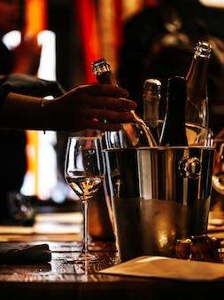 ワインの試飲:木製のテーブルの上にワインを一杯、そしてワインを冷やすための銀製のバケツがあります