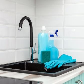 台所を掃除するための青い掃除用具と道具のセットが台所の流しの近くにあります。