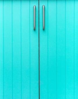 クロムハンドルが付いている細いストリップから成っている食器棚の青い木製の正面。