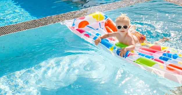 かわいい女の子は、プールのエアマットレスで泳ぎます。トップビュースペースをコピーします。