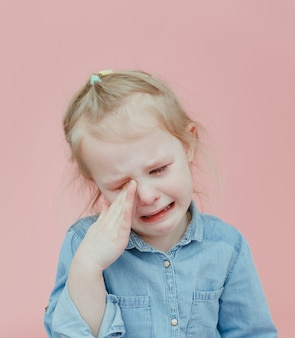 Очаровательная маленькая девочка в джинсовой одежде плачет на розовом