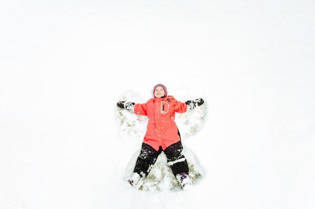 ピンクの冬の子供が楽しんで、雪の上に横になって、腕と脚を離しています。