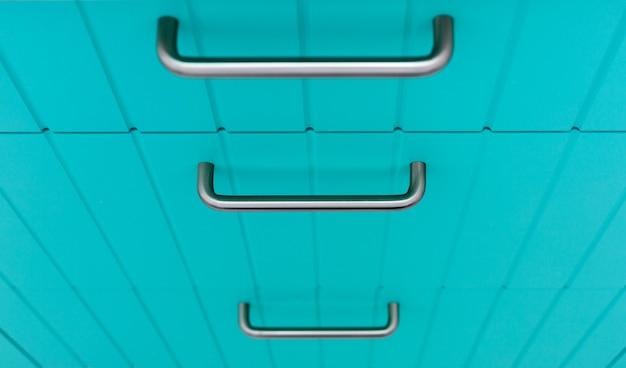 クロムハンドルが付いている食器棚の青い木製の正面。