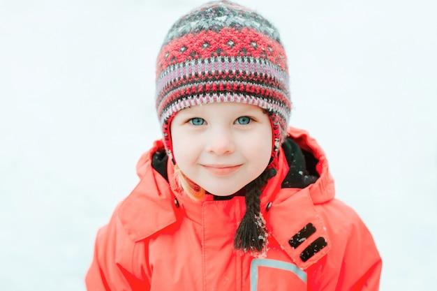 笑みを浮かべて、雪の中で笑っているニットの冬の帽子とピンクのジャンプスーツで、かなり白い女の子