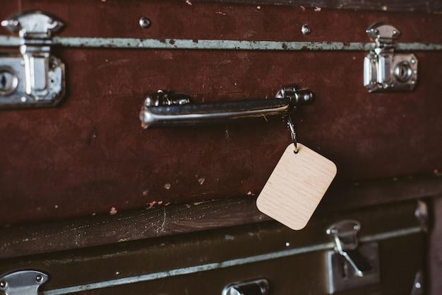 古いスーツケースのハンドルに木製の荷物タグ。モックアップ