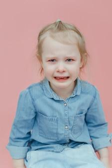 Очаровательная маленькая девочка в джинсовой одежде плачет.