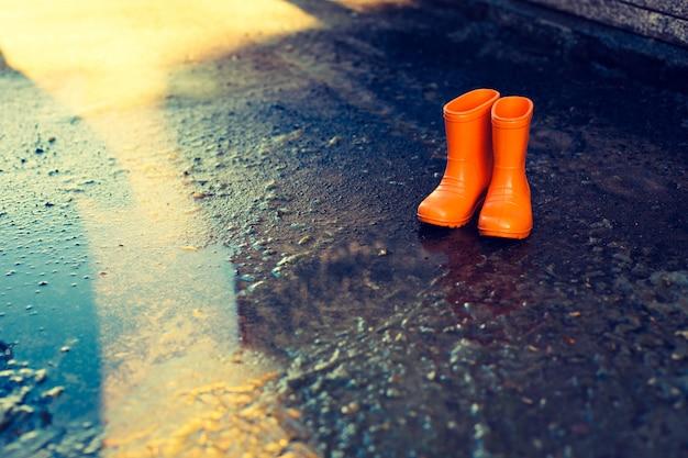 水たまりのそばに立っているオレンジ色のゴム長靴。