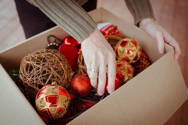 クリスマスツリーの飾り用のおもちゃで段ボール箱からクリスマスボールを取り出す人