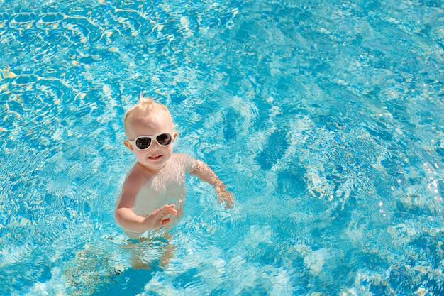 Милый маленький ребенок с солнцезащитные очки, счастливо брызг в бассейне.