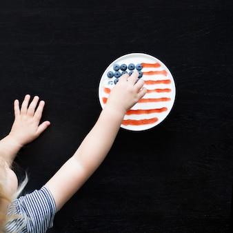 赤ちゃんはアメリカの国旗でレイアウトされた食事と一緒にボウルからベリーを取ります。独立記念日のコンセプトです。