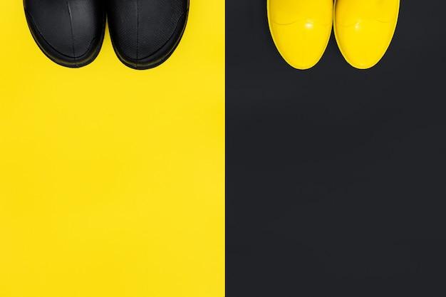 Вид сверху модные мужские и женские резиновые сапоги на контрастном фоне. концепция осени