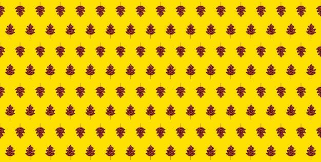 Бесшовный осенний узор-желтый фон с осенними листьями из вязаного шарфа.