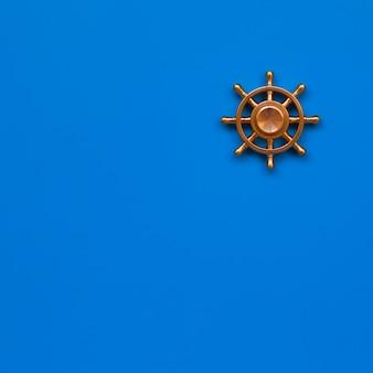 青色の背景に銅ヨットステアリングホイール