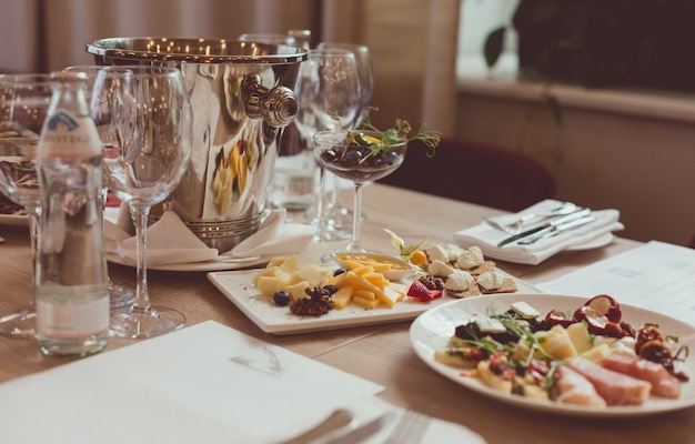 Столовые приборы, закуски, плевательница и стаканы на деревянном столе в ресторане