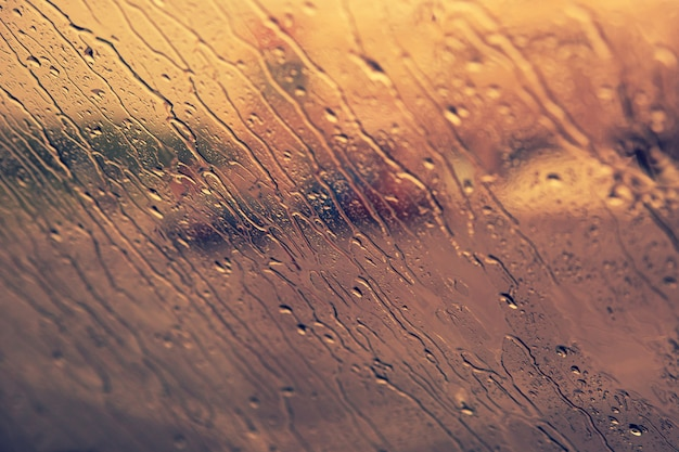Стекающие капли дождя на лобовом стекле. концепция падения