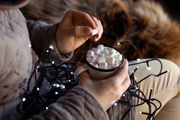 ホットチョコレートの白いエナメルマグカップを持つ女性の手